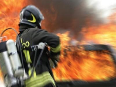 Vigile del fuoco doma l'incendio di un'auto
