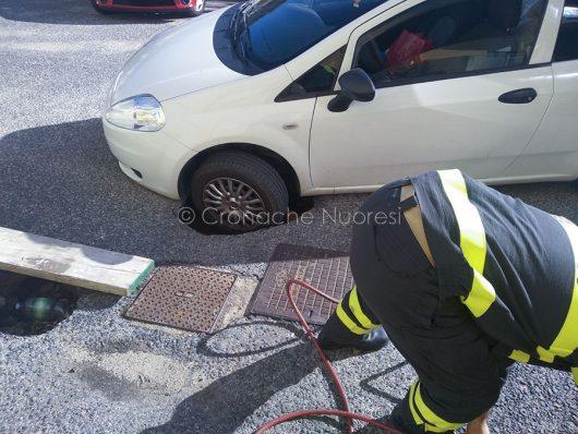 L'auto con la ruota dentro la buca (foto Cronache Nuoresi)